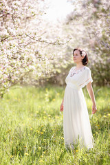 Beautiful young woman in apple blossom garden