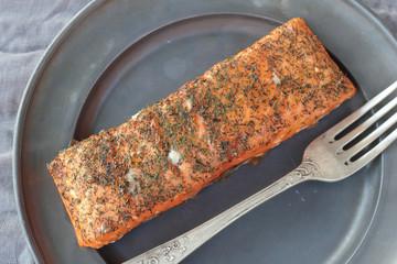 Nice piece of smoked salmon seasoned with salt and chopped dill.