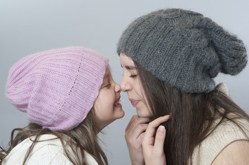 Young girl and baby nose to nose..