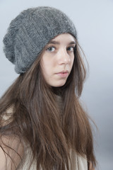 Young brunette girl in a knitted hat..