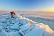 Leinwandbild Motiv Photographer take pictures on the river bank in winter