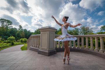 Ballerina dancing near columns, in pointe position. Outdoors