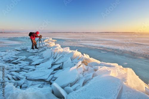 Fotograf robi zdjęcia na brzegu rzeki w zimie
