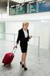 Frau mit Koffer und Handy am Flughafen