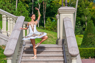 Ballerina stands on stairs, standing in pointe position. Spring