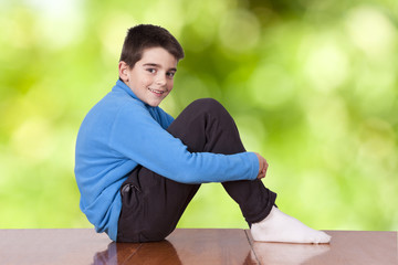 boy sitting on the table outdoors