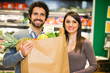 Young couple holding a shopping bag in a supermarket