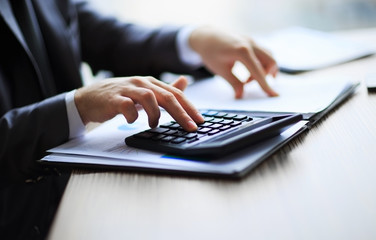 Business people counting on calculator sitting
