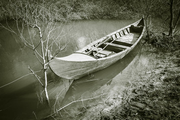 monochrome of a Canoe parked in the shore of a river