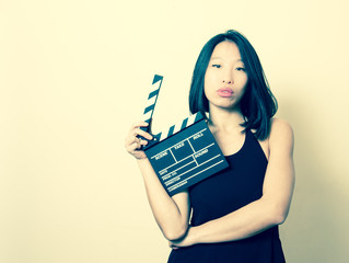 Young seductive asian woman with clapperboard vintage colors