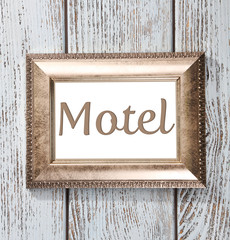Word Motel in frame on wooden background