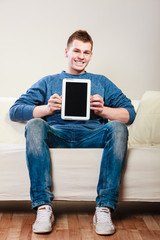 Young man with tablet sitting on couch at home