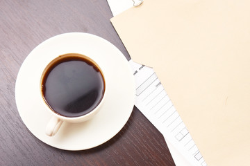 A folder with papers and a cup of coffee on a desk