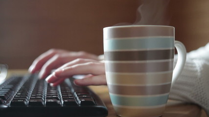Striped mug of coffee on the table and keyboard close up