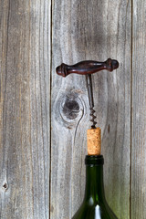Vintage corkscrew removing cork from wine bottle with wood backg