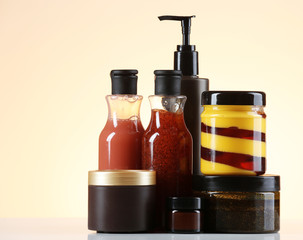 Cosmetic bottles on light colorful background