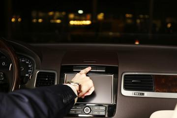 Man driving his modern car at night in city, close-up