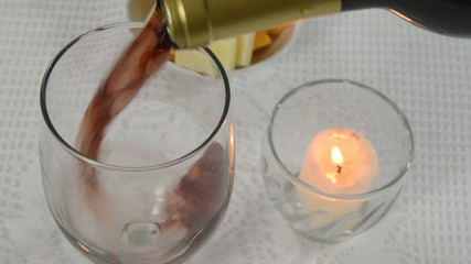 Placing a candle on a table and pouring Burgundy wine