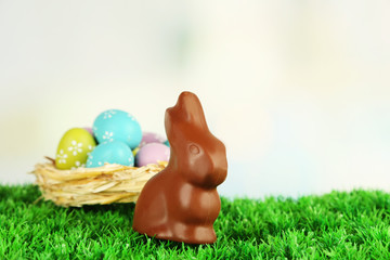 Easter composition with chocolate rabbit on green grass