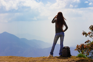 Woman Traveler with Backpack looking at mountain landscape and