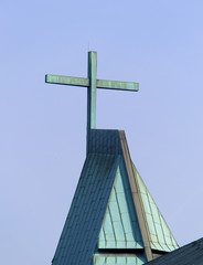 Roof of a Roman Catholic church with cross, covered with patina