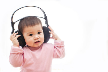 One small happy baby girl listens music song with headphone