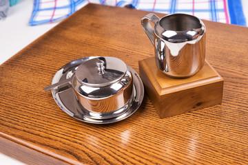 металическая посуда на фоне деревянном