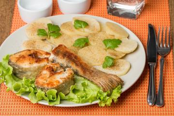 White fish with potato on white plat