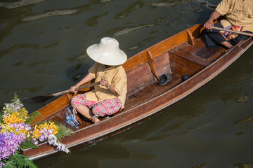 man paddling in the floating market in Thailand