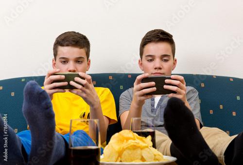 Leinwanddruck Bild Zwei Jungen mit Smartphone auf der Couch