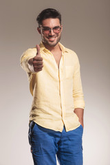 casual man smiling showing the thumbs up gesture.