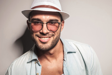 handsome casual man wearing a white hat and sunglasses.