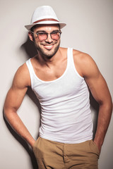 Smiling young fashion man leaning on a white wall