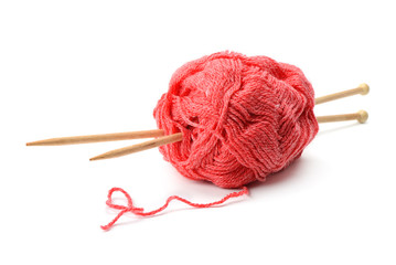 Woolen balls and knitting needles on white
