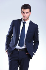 Attractive business man posing on grey studio background