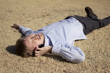 公園に寝転がりながらスマートフォンで話す男性