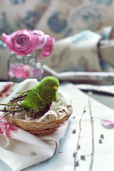 Easter decoration - bird in a nest with lace, pink roses and wil