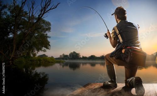 Papiers peints Peche Young man fishing at misty sunrise