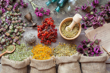 Healing herbs in hessian bags, wooden mortar, small bottles on o