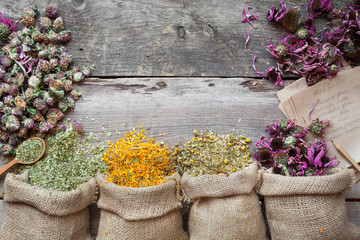 Healing herbs in hessian bags on old wooden rustic table, herbal