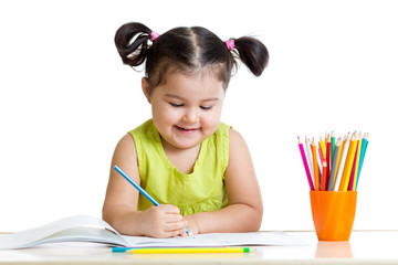 Cute kid drawing with colorful pencils and smiling