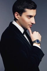 Handsome young man in suit with watch on white background.