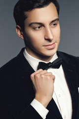 Close-up portrait of handsome young man in suit and bow tie on w