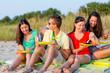 smiling friends sitting on summer beach