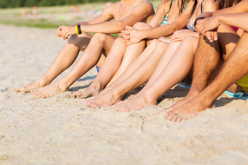 close up of friends sitting on summer beach