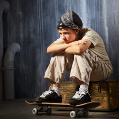 sad teenager sitting on skateboard