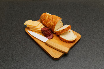 Bread, salami and cheese on the wooden plate