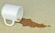 A spilled cup of coffee on a carpet with stain - 78621119
