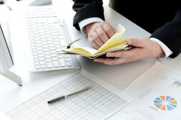 ビジネスイメージ―手帳をチェックするビジネスマン
