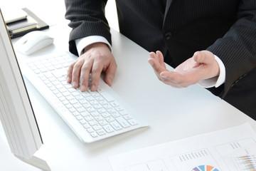 ビジネスイメージ―パソコンを見ながら説明をするビジネスマン